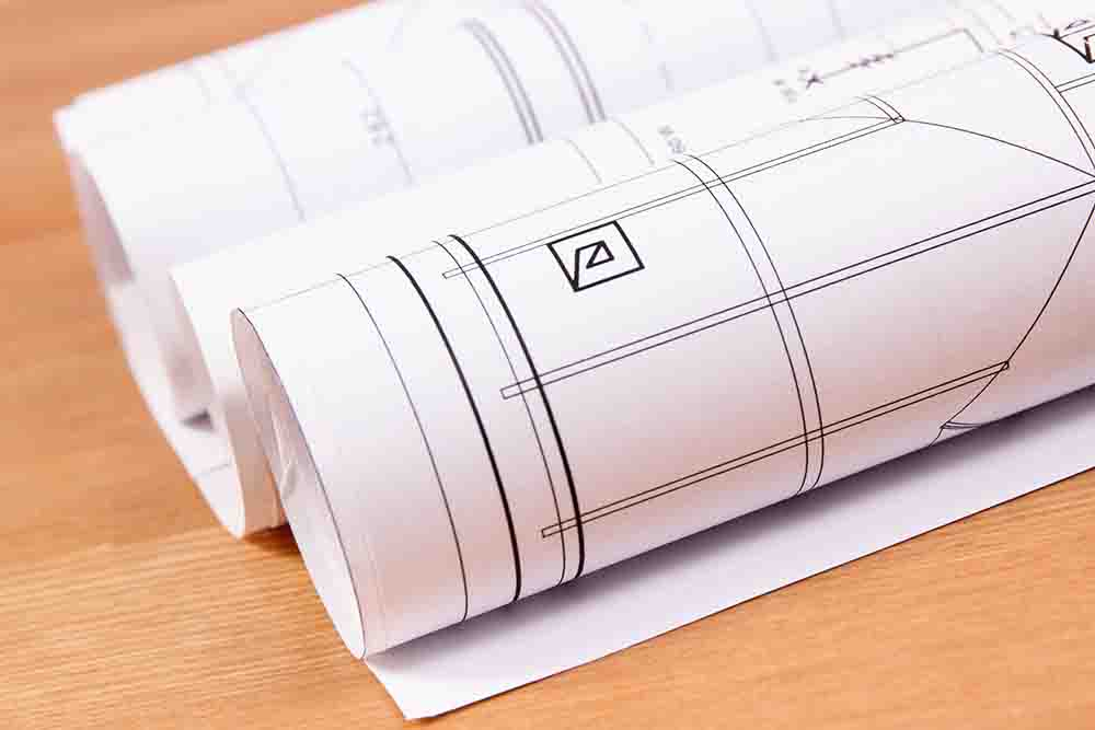 Rolls of electrical diagrams for engineer jobs lyin on desk